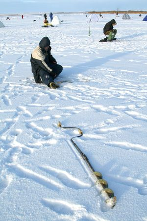 Fishing drill on an ice of the frozen lake photo