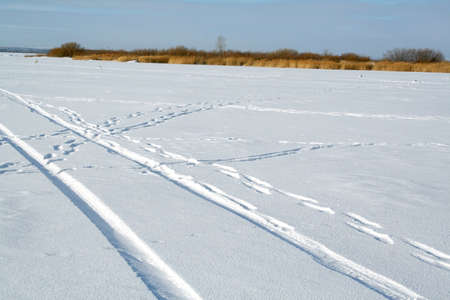 sidelit: Abstract design - tire tracks in snow. Winter landscape