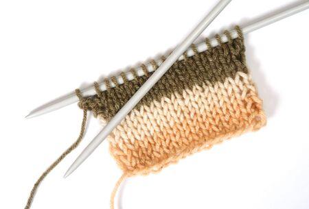 Breierei een kleur pluizig wooll, met breinaalden. Geïsoleerd op wit