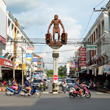 neanderthal: 29 November, 2014: Street art, Statue of Neanderthal man, unusual traffic lights in Krabi town, Thailand Editorial