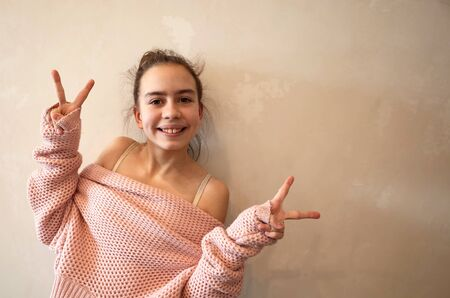 Portrait of pretty positive happy teenage girl gesturing peace dressed in pink knitted loose sweater. Toned photo with copy space on background of grunge beige wall Banco de Imagens