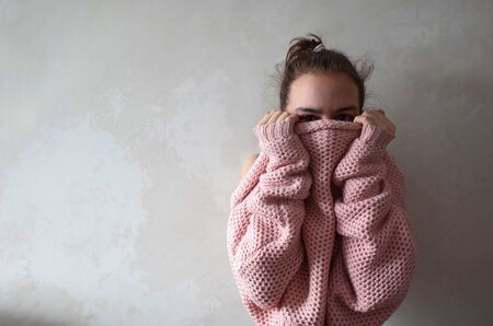 Portrait of thirteen year old girl hiding her face in warm pink knitted loose sweater. Photo with copy space on background of grunge white wall Banco de Imagens