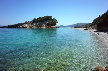 Picturesque turquoise clear water and beautiful small island in Aegean Sea near Kokkari village on Samos Island, Greece