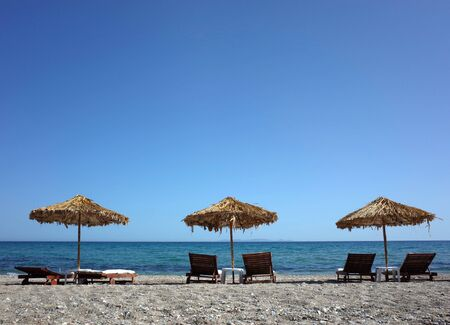 Loungers under palm tree leaves parasols on beach on Samos island, Greece Banco de Imagens