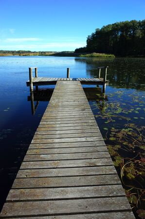 Long wooden bridge in lake with calm water and blue sky in Sweden, Scandinavia, Europe. Peaceful outdoor image on Malaren lake in Vastmanland