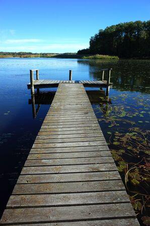Long wooden bridge in lake with calm water and blue sky in Sweden, Scandinavia, Europe. Peaceful outdoor image on Malaren lake in Vastmanland Banco de Imagens - 127345265
