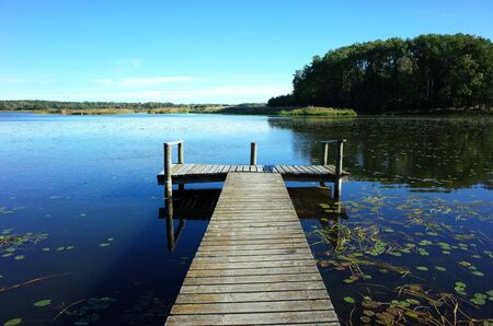 Small wooden bridge in lake with calm water and blue sky in Sweden, Scandinavia, Europe. Peaceful outdoor image on Malaren lake in Vastmanland