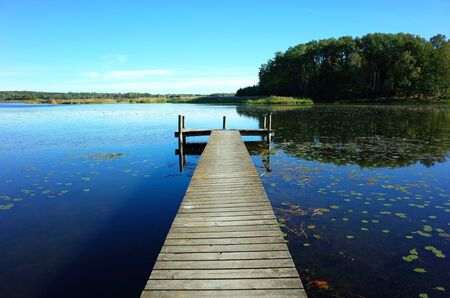 Wooden bridge in lake with calm water and blue sky in Sweden, Scandinavia, Europe. Peaceful outdoor image on Malaren lake in Vastmanland 版權商用圖片