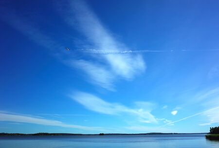 Small airplane flying with trail on background of beautiful light clouds on blue sky over Malaren lake in Sweden Banco de Imagens - 127345343