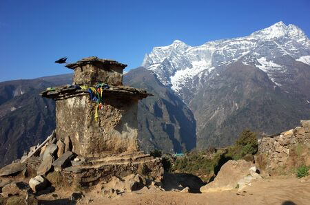 Black bird started flying from old buddhist stupa in Himalaya mountainst, Sagarmatha national park, Khumbu valley, Nepal. Mount Kongde on background