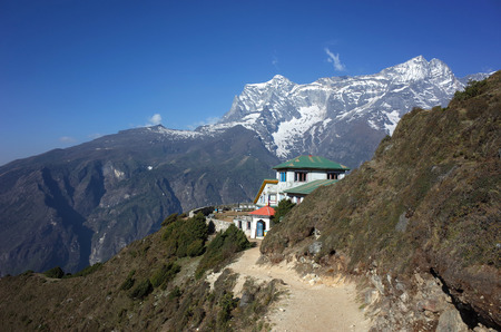 Himalayas mountains landscape with trail to guest house hidden half behind green hill and view of Kongde mountain 新聞圖片