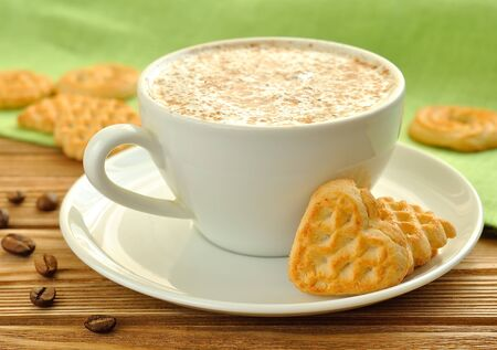 Cappuccino and cookies on a brown table photo