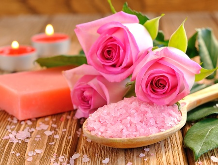Sea salt, rose, soap and a burning candle on a brown table photo