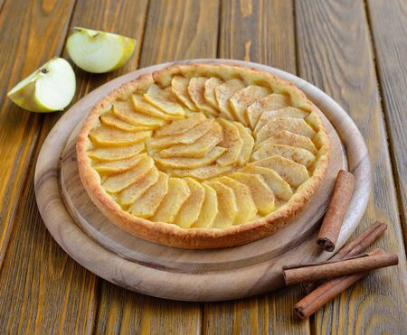 Tart with apples and cinnamon on a brown table