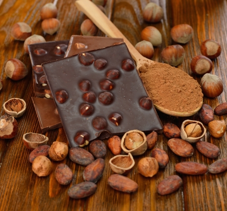 Chocolate with hazelnuts and cocoa beans on a brown table Stock Photo - 16885219