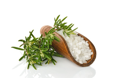 Salt in a wooden scoop and rosemary on a white background photo