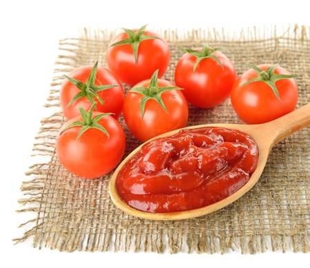 salsa de tomate: Salsa de tomate y tomates maduros sobre fondo blanco