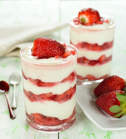 Dessert with strawberries in a glass on a white table Stock Photo