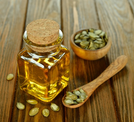Pumpkin seed oil in a glass bottle on a brown table