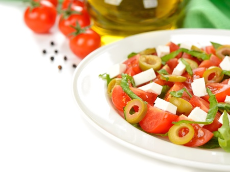 Fresh salad of tomatoes, olives and cheese on white background