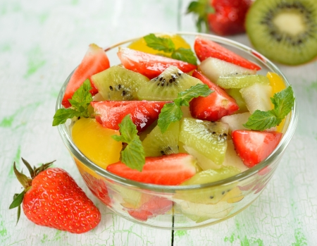 Fruit salad in a glass bowl on a white table photo