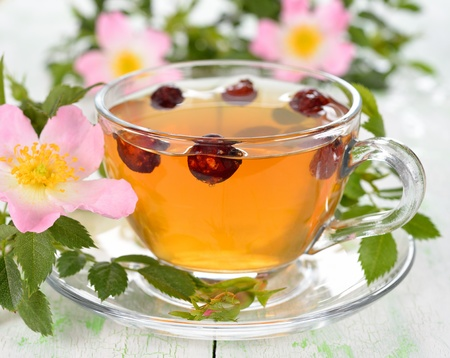 Tea with rosehip in a glass cup on white table