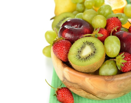 Various fruit in a wooden bowl on a white background photo