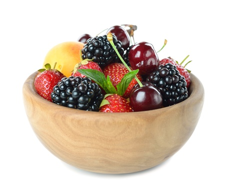 Various fruit in a wooden bowl isolated on a white background photo