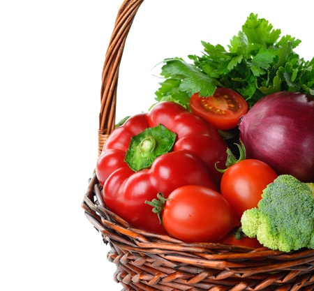 Various vegetables in a brown basket isolated on white background photo