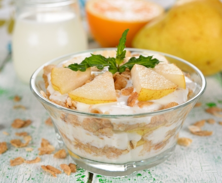 Dessert of muesli and yogurt with pear on a white table photo