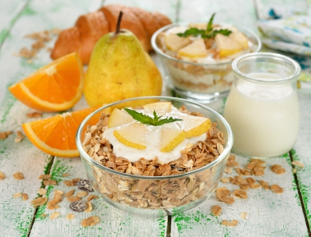 Muesli with yogurt and pear on a white table photo