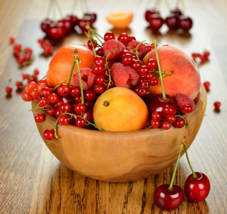 Fruit in a wooden bowl on a brown table photo