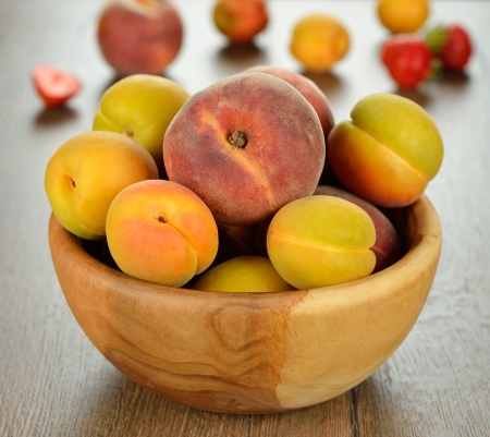 Peaches and apricots in a wooden bowl on a brown table photo