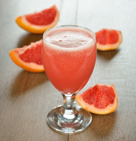 Fresh grapefruit juice on a brown table