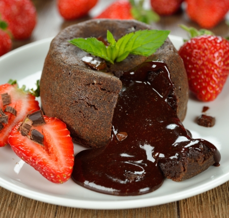 Cake with chocolate and strawberries on a brown background