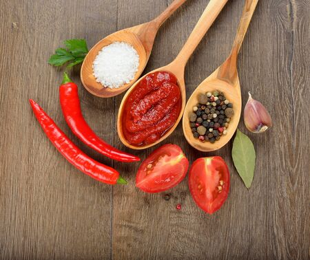 Spices, salt and tomato sauce in wooden spoon on brown background photo