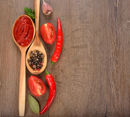 Tomato ketchup, spices and vegetables on a brown background Stock Photo - 21718131