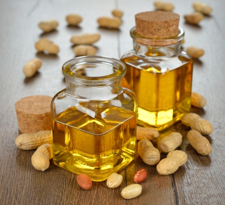Peanut oil in a glass bottle on a brown background Stock Photo