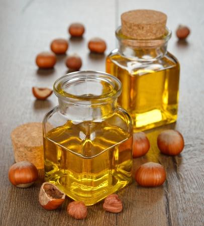 Hazelnut oil in a glass bottle on a brown background