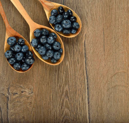 Blueberries in a wooden spoon on a brown background photo