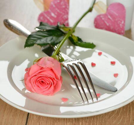 diner romantique: Couverts et rose sur une plaque blanche