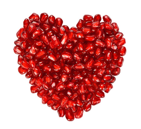 Heart from pomegranate seeds isolated on white background photo