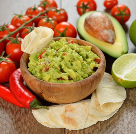 Guakamole and fresh vegetables on brown