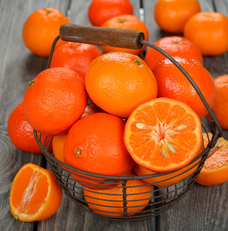 saturated color: Fresh tangerines in the basket on a gray background