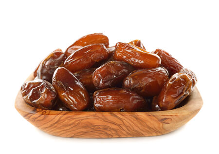 dried dates in a wooden bowl isolated on white  photo