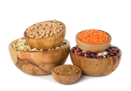 Various legumes in wooden bowl isolated on white background photo