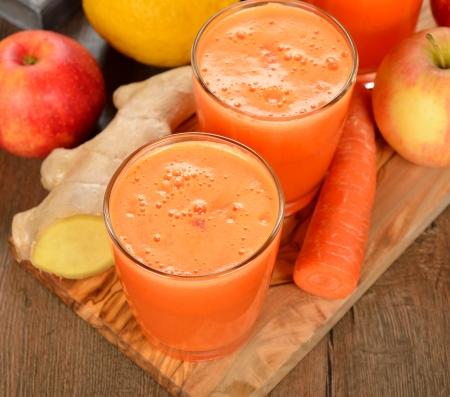 jus orange glazen: Frisse appel en wortelsap op bruine achtergrond