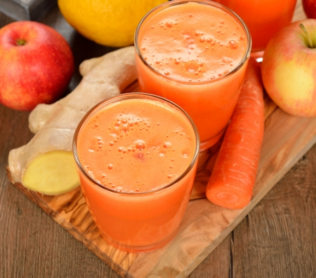 zanahoria: Manzana fresca y jugo de zanahoria sobre fondo marr�n Foto de archivo