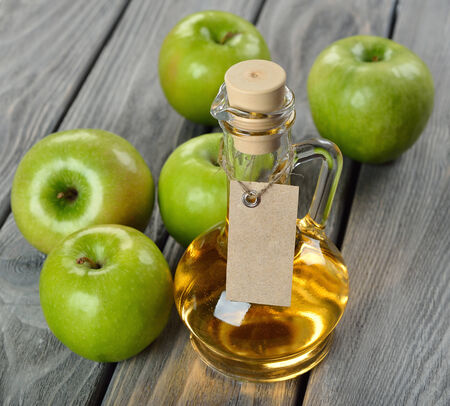 Natural apple cider vinegar on a gray background photo