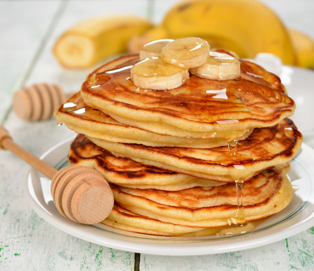 Pancakes with banana and honey on a white background